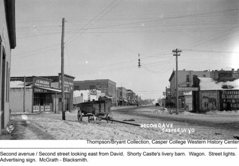 Second Avenue, Second Street looking East from David. Shorty Castle's livery barn. Wagon. Street lights. Advertising sign, McGrath, Blacksmith. Thompson/Bryant Collection, Casper College Western History Center