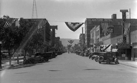 Center Street. Casper, Wyoming. Gladstone Hotel, Townsend Hotel. Flags hanging between buildings.